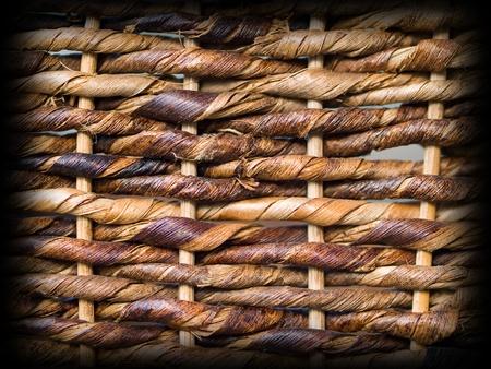暗いエッジの縁取りと茶色の枝編み細工品バスケット パターン バック グラウンド テクスチャを織り 写真素材