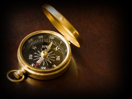 Koperen kompas op een oude kersenhouten tafel met een donkere rand