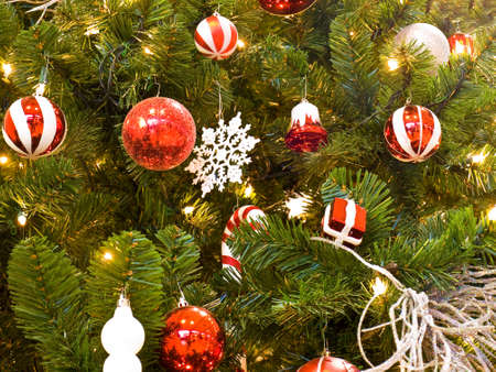 red and white christmas ornaments on a green tree with white lights stock photo 9815720