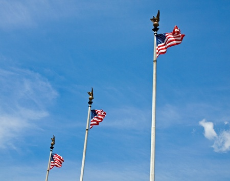 Three American Flags Waving Proudly on Tall Flagpoles photo