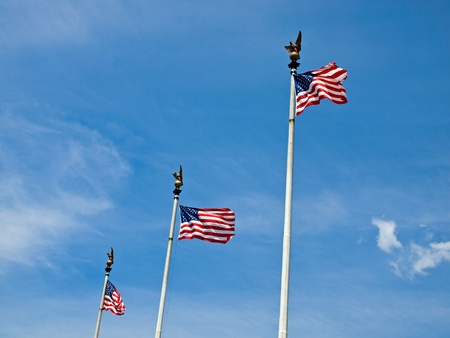 flagpoles: Three American Flags Waving Proudly on Tall Flagpoles