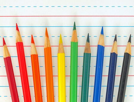 Rainbow of Colored Pencils Isolated on Lined Paper photo