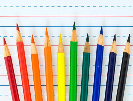 penmanship: Rainbow of Colored Pencils Isolated on Lined Paper
