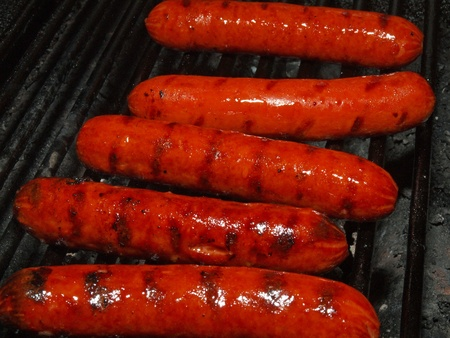 A row of five hotdogs on a bbq grill