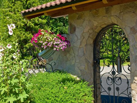 Wrought Iron Garden Gate in a Fancy Garden Stock Photo - 10754555