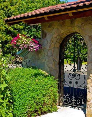 Smeedijzer Garden Gate in een Fancy Tuin Stockfoto