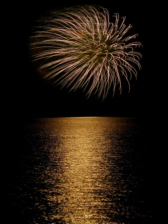 Long Exposure of Fireworks Reflecting on Calm Rippling Water photo