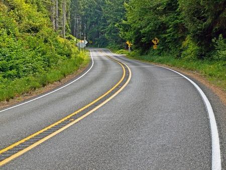 Gebogen Twee Lane Country Road Winding door een bos Stockfoto