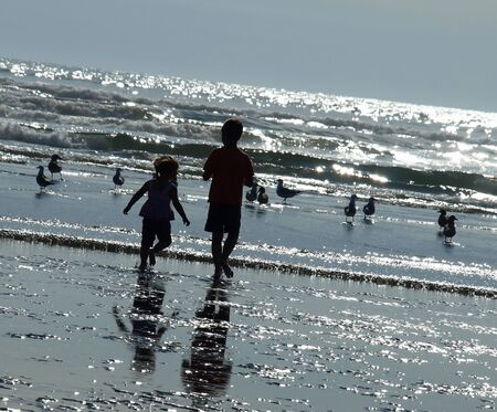 Two Kids Playing on the Beach as the Sun is Glistening on the Water photo
