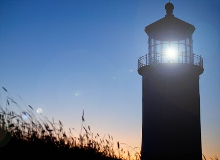 guiding: Light Shining in the North Head Lighthouse on the Washington Coast at Sunset  Stock Photo