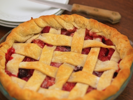 Fresh Baked Three-Berry Pie with Lattice Crust with Plates and Knife photo