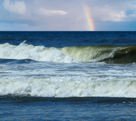 Ocean Waves Breaking on Shore with a Partial Rainbow in the Background Stockfoto
