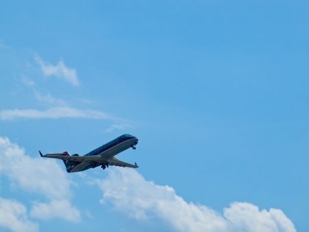 A Commercial Airliner Taking Off into a Partly Cloudy Blue Sky photo