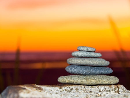 Stack of Five Flat Rocks on the Beach at Sunset photo