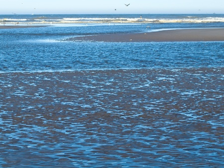 Ocean Ripples in Shallow Water with Waves in the Background photo