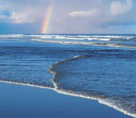 Ocean Waves Breaking on Shore with a Partial Rainbow in the Background Standard-Bild