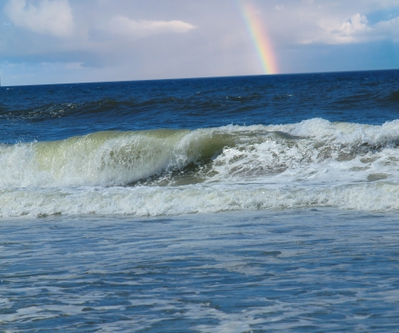 Ocean Waves Breaking on Shore with a Partial Rainbow in the Background   photo