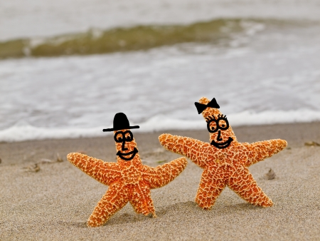 Two Orange Starfish with Smiling Faces on the Shoreline with Waves in the Background photo
