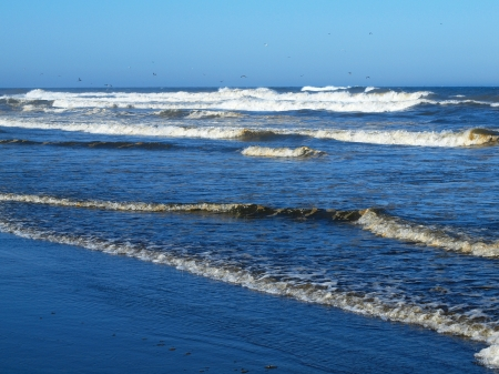 Ocean Waves Breaking on Shore on a Clear, Sunny Day photo
