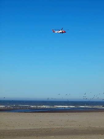 evacuating: A Coast Guard Helicopter Patrolling the Shoreline on a Clear Day