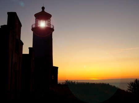 Lighthouse with Lens Flare on the Washington Coast at Sunset photo