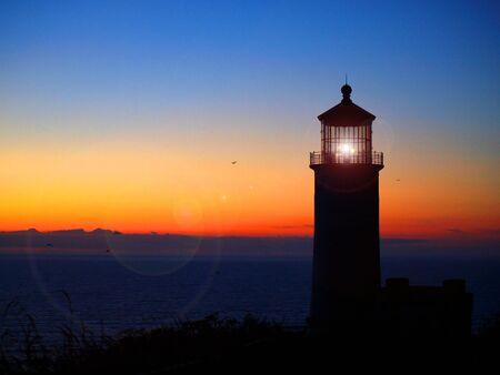 guiding light: Lighthouse with Lens Flare on the Washington Coast at Sunset Stock Photo