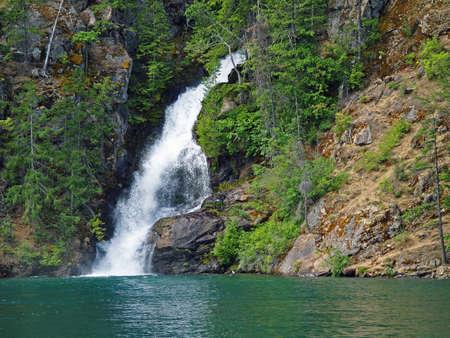 Beautiful Mountain Waterfall Flowing into a Green Lake photo