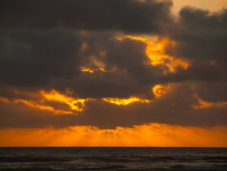 Golden Sunset with Clouds  Over the Ocean at the Beach photo