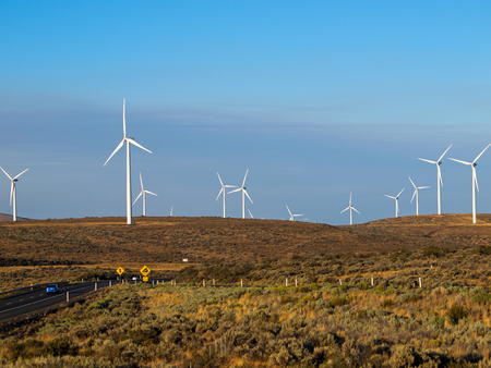 industrial park: A Windmill Farm on a Mountain Beside an Interstate Highway at Dusk Stock Photo