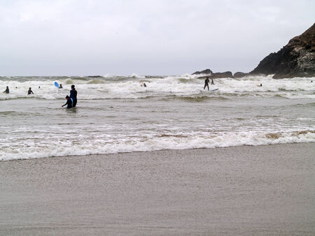 surfboard fin: Surfers in Wetsuits Surfing on a Cloudy Day on the Oregon Coast Editorial