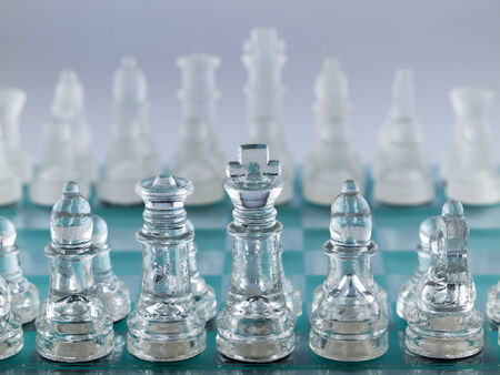 Glass Chess Pieces on a Frosted Glass Chessboard photo
