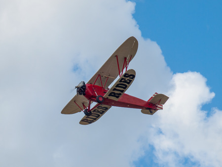 A Biplane in Flight Giving Rides in a Blue Sky and Some Fluffy Clouds
