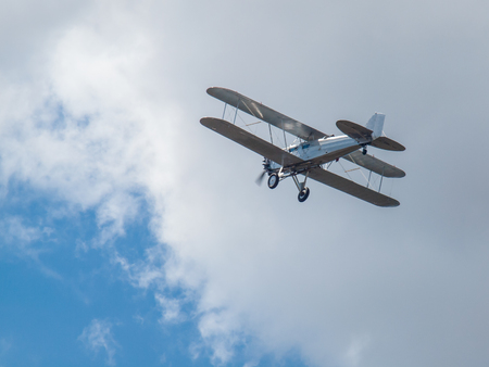 A Silver Biplane in Flight in a Blue Sky and Some Fluffy Clouds
