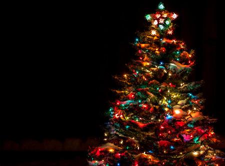 Sneeuw bedekte kerstboom met Multi gekleurde lichten Stockfoto