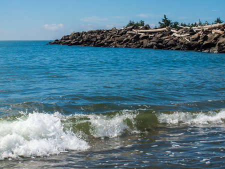 Gentle Beach Waves with a Rock Jetty photo