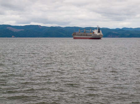 Cargo Ship on the Columbia River under Cloudy Skies at Astoria Oregon USA