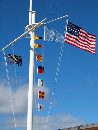 Nautical and American Flags Flying from a Ships Mast with Wispy Clouds and Blue Sky