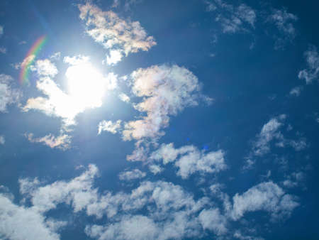 A Bright Sun Behind Some White Clouds Stock Photo