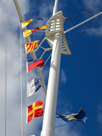 Nautical Flags Flying from a Ships Mast with Wispy Clouds and Blue Sky photo