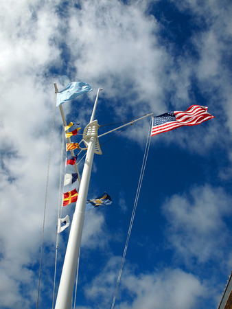 Nautical and American Flags Flying from a Ships Mast with Wispy Clouds and Blue Sky photo