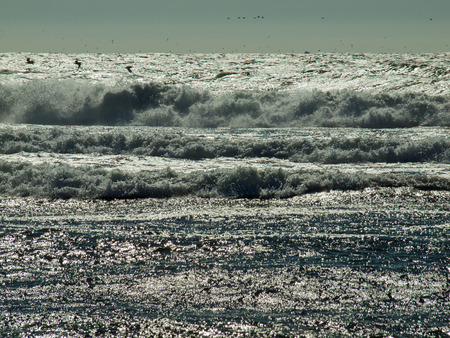 Waves Crashing on the Shore with the Sun Shining on the Surface