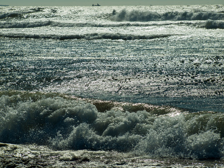Waves Crashing on the Shore with the Sun Shining on the Surface photo