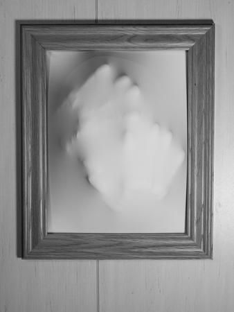 haunt: Creepy Bland and White Picture Frame with Something Coming Out of It Stock Photo