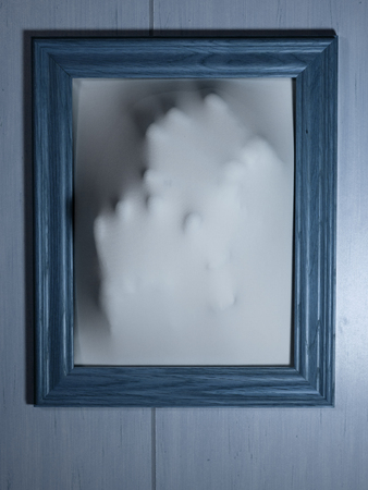 haunt: Creepy Bluetone Picture Frame with Something Coming Out of It