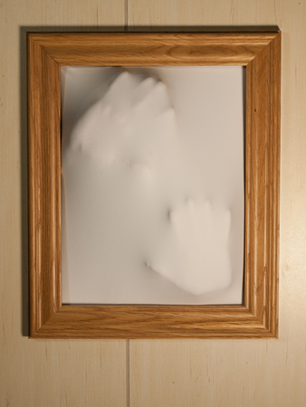 haunt: Creepy Picture Frame with Something Coming Out of It Stock Photo