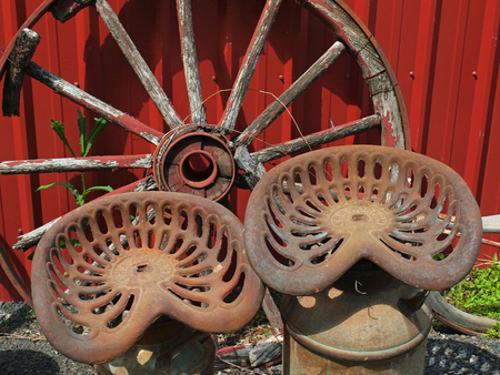 Old Wooden Wagon Wheel and Two Metal Seats Stock Photo