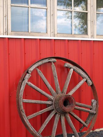 carreta madera: Rueda de carro de madera vieja que se inclina contra una pared roja