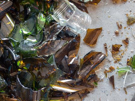 Broken Glass Bottle Pieces on a Cement Floor