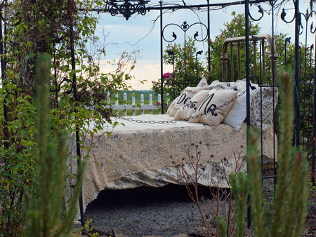 lacey: An Outdoor Bed with Lacey Blankets and Wedding Pillows Stock Photo