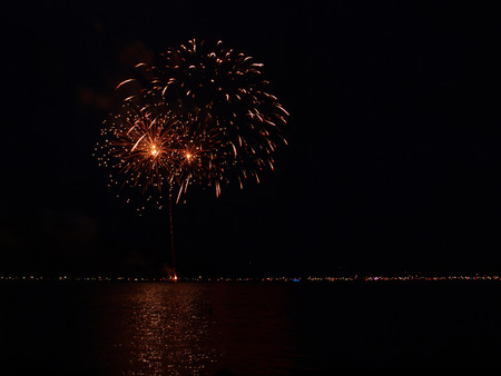 reflecting: Long Exposure of Fireworks Reflecting on Calm Rippling Water